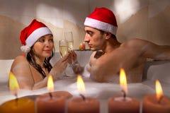 Couple in santa hats is enjoying a bath Stock Photos