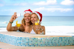 Couple with Santa hats holding cocktails Royalty Free Stock Photography