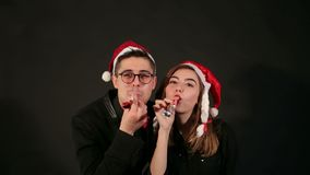 Couple in Santa hats with Holiday horns at party. Portrait of a couple in Santa hats on a black background, they blow in pipe the whistle celebrating a new year stock video