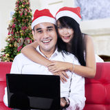 Couple in santa hats with a laptop Stock Images