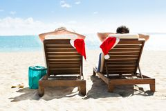 Couple with santa hats relaxing on deck chairs at beach resort Stock Photo