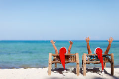 Couple in Santa hats on tropical beach. Happy romantic couple in red Santa hats at tropical beach relaxing on sun beds Stock Image