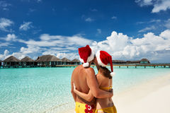 Couple in santa's hat on a beach at Maldives Stock Photos