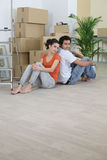 Couple sat back to back on floor Stock Image