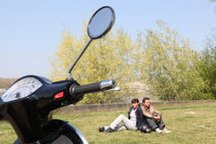 Couple sat near scooter Stock Photography