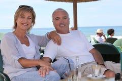 Couple sat on hotel terrace Stock Photo
