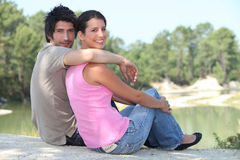 Couple sat by lake Stock Images