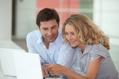 Couple sat with laptop. Couple at work on laptops Royalty Free Stock Image