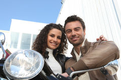 Couple sat on scooter Stock Photo
