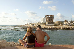 A couple sat by the sea, Beirut. Waterfront Royalty Free Stock Photo