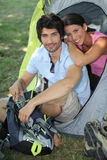 Couple sat by tent royalty free stock photography