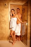 Couple at sauna door. Couple standing at sauna door, smiling after relaxing in steam, leaving Royalty Free Stock Images