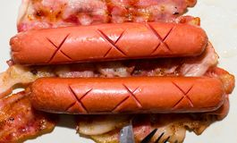 Couple of Sausages over Bacon Royalty Free Stock Images