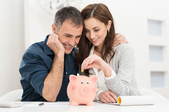 Couple Saving Money. Portrait Of Happy Couple Inserting Coin In Piggybank Royalty Free Stock Images