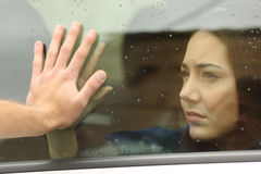 Couple saying goodbye before car travel. Holding hands through the window Stock Photos