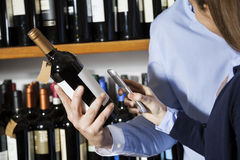 Couple Scanning Barcode On Wine Bottle Through Smartphone Stock Photo
