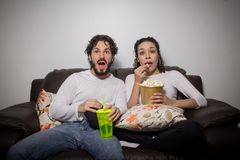 Heterosexual couple is eating popcorn and watching movie at home. Couple is scared of the horror movie. Man and women are at home eating popcorn and watching Stock Photography