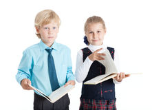 Couple of school pupils holding opened books for reading, looking at camera, isolated white background Royalty Free Stock Images