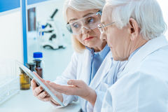 Couple of scientists working with digital tablet in lab Stock Photos