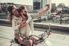 Couple on scooter. Beautiful young couple in sun glasses is doing selfie using a smart phone and smiling while sitting on a scooter outdoors Royalty Free Stock Image