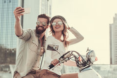 Couple on scooter. Beautiful young couple in sun glasses is doing selfie using a smart phone and smiling while sitting on a scooter outdoors Stock Photo