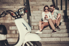 Couple with a scooter. Beautiful young couple in sun glasses is using a smart phone and smiling while sitting on stairs outdoors Royalty Free Stock Images