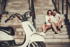 Couple on scooter. Beautiful young couple is using a smart phone and smiling while sitting on stairs outdoors, scooter in the foreground Stock Photography
