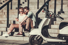 Couple with a scooter. Beautiful young couple is using a smart phone and smiling while sitting on stairs outdoors, scooter in the foreground Royalty Free Stock Images