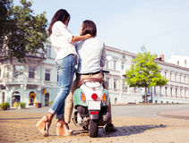 Couple on scooter enjoying themselves. Portrait of happy young couple on scooter enjoying themselves in european city Royalty Free Stock Photography