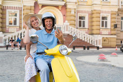 Couple on scooter with phone. Royalty Free Stock Photos
