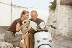 Couple With Scooter Reading Map In Granada Royalty Free Stock Photos