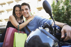 Couple With Scooter And Shopping Bags Standing Together Royalty Free Stock Photo