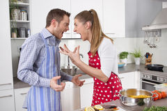 Couple screaming at each other at kitchen - stress. Stock Photo