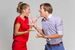 Couple screaming at each other. Young couple screaming at each other over grey background Stock Photography