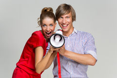 Couple screaming at megaphone Stock Photo
