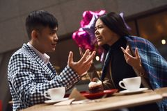 Couple screeches in coffee shop at table. Stock Image