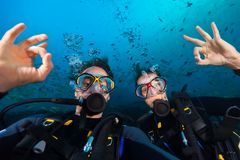 Couple of scuba divers showing ok sign, portrait photography. Underwater sports and activities Stock Photography