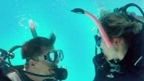 Couple in scuba gear looking at each other underwater stock video