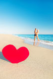 Couple at sea beach and big red heart Royalty Free Stock Photos