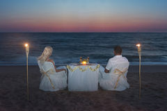 Couple at sea beach during luxury romantic dinner, with candles Stock Photos