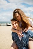 Couple on sea side. Teenage boy giving piggyback ride to her girlfriend by the sea Stock Images