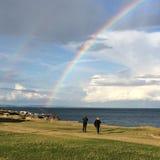 Couple by sea watching rainbow. Stock Image