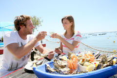 Couple in seafood restaurant making toast Royalty Free Stock Images