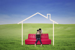 Couple search online for dream house. Asian couple is using laptop to search for dream house on green field Royalty Free Stock Image
