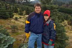 Couple search for perfect Christmas tree to cut. Middle aged couple search for the perfect Christmas tree to cut down at a christmas tree farm in the foothills stock photos