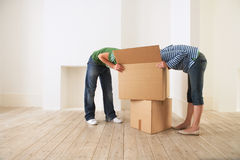 Couple Searching Into Cardboard Box. Young couple searching into cardboard box in new home Royalty Free Stock Image