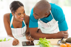Couple searching recipe. Lovely young african american couple searching for a recipe on tablet computer Stock Photo
