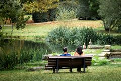 Couple Seated on the Bench in the Park stock images