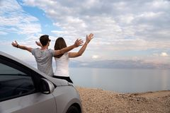 Couple seated on the engine hood of a rented car on a road trip in israel royalty free stock photo