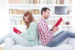 Couple is seated together on a couch back to back and they are r. Young, attractive couple is seated together on a couch back to back and they are reading a book stock photo